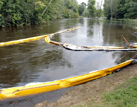Booms along the Kalamazoo River attempt to contain some surface oil.   After more than 3 years and $1 billion in clean up and remediation efforts, more than 20% of the lost dilbit remains adhered to sediments in the riverbed.